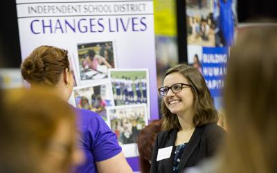 A student talks to a recruiter at a teacher career fair