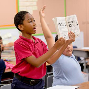 child holding a book up in a classroom