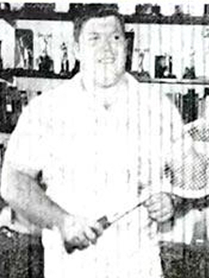 black and white photo of Terry Todd in the 1950s holding a tennis racket.