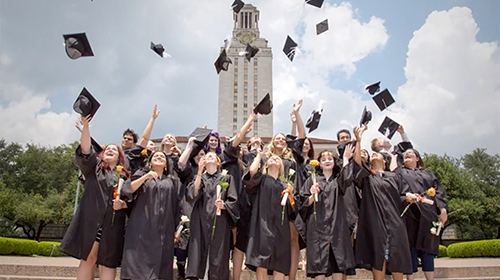 A group of UTHS graduates celebrate commencement in front of the Tower.